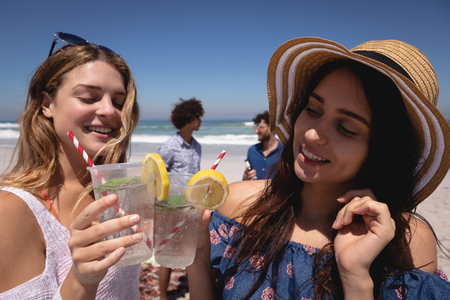 Front view of beautiful young Multi ethnic woman toasting cocktail glasses at beach in the sunshine with two of their friends in background