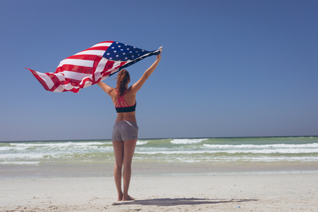 Rear view of young Caucasian woman holding american flag at beach on a sunny day