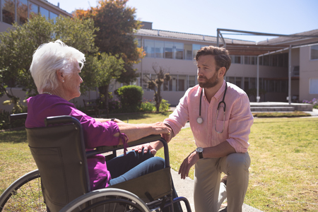 Side view of a Caucasian male doctor talking with disabled senior patient women in wheelchair against retirement house in background