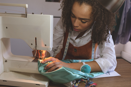 Front view of young Mixed-race female fashion designer working with sewing machine Banco de Imagens