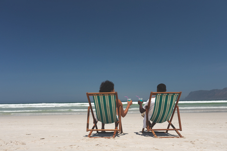 Rear view of young multi-ethnic couple relaxing on sun lounger at beach on sunny day, They are drinking a cocktails