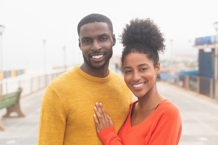 Portrait of romantic Multi-ethnic couple standing at promenade near sea side. They are smiling and looking at camera
