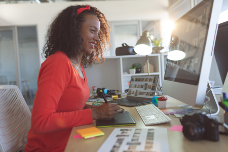Side view of happy young mixed-race female graphic designer using graphic tablet at desk in a modern office Archivio Fotografico