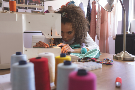Front view of young Mixed-race female fashion designer working with sewing machine Stock fotó