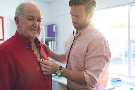 Front view of confident Caucasian male doctor checking Caucasian senior patient heartbeats in clinic