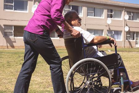 Side view of senior Caucasian woman pushing senior man on wheelchair at backyard nursing park Imagens