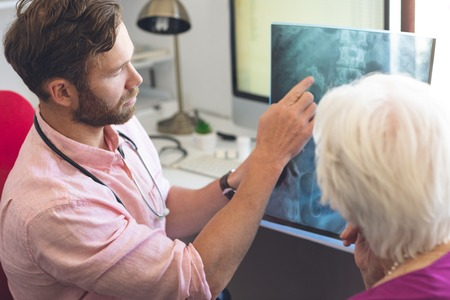 High angle view of a Caucasian male doctor and a Caucasian senior female patient discussing over x ray in clinic