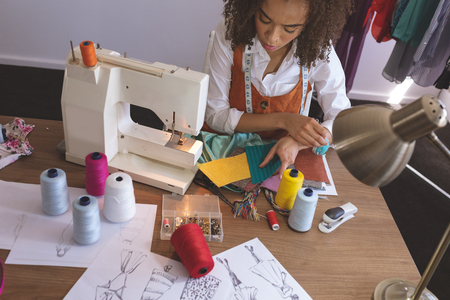 High angle view of young Mixed-race female fashion designer working in design studio 写真素材 - 121757468