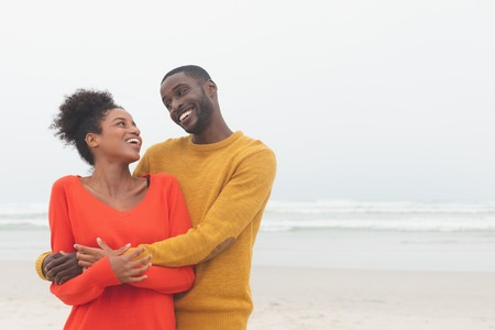 Front view of cute Multi-ethnic couple standing and looking at each other at beach on a sunny day. They are smiling