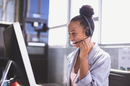 Seitenansicht einer jungen gemischtrassigen Geschäftsfrau, die über ein Headset spricht, während sie am Computer am Schreibtisch im Büro arbeitet