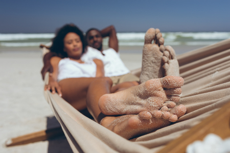 Front view of romantic young multi-ethnic couple relaxing on hammock at beach on sunny day. They seem happy