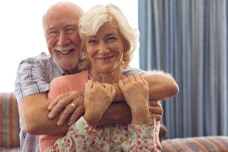 Portrait of happy Caucasian senior couple sitting on sofa at retirement home