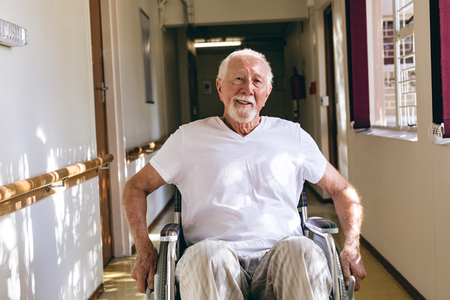 Front view of senior Caucasian male patient sitting in wheelchair in corridor at retirement home