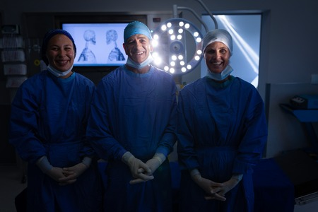 Front view of Caucasian surgeons smiling to the camera with hands crossed in the operation theater in a clinic.
