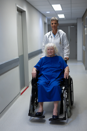 Portrait of a mature Caucasian female doctor pushing a senior Caucasian female patient sitting in a wheelchair while they are looking at the camera in clinic