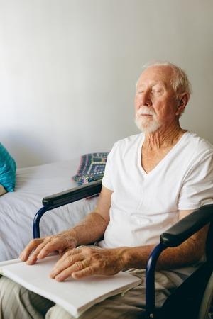 Front view of blind senior Caucasian man using braille to read in a retirement home