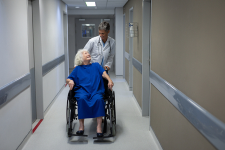 Front view of a Caucasian female doctor talking with a disabled senior Caucasian female patient in clinic at hospital