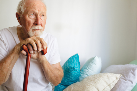 Front view of senior Caucasian male patient sitting upset on bed with stick at retirement home 免版税图像