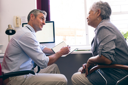 Side view of male Caucasian doctor prescribing medicine to senior African American woman in clinic at retirement home