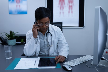 Front view of confident Asian male doctor talking on mobile phone while using digital tablet in clinic at hospital Stock Photo