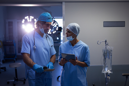 Front view of Caucasian surgeons interacting with each other while holding digital tablet at hospital