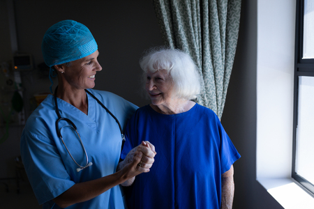 Front view of a Caucasian female surgeon and a senior Caucasian patient talking with each other in clinic next to a window at hospital