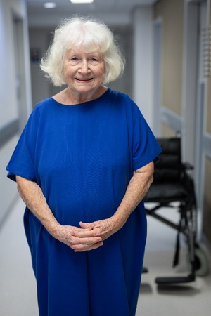 Portrait of a senior Caucasian female patient looking at the camera while standing with hands joined in hospital clinic
