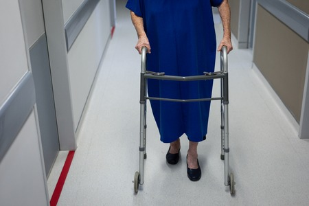 Low section of a senior Caucasian female patient walking with a walker in the clinic corridor