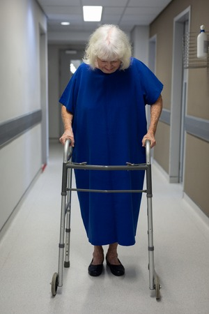 Front view of a senior Caucasian female patient walking with a walker in the clinic corridor