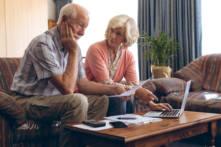 front view of Caucasian senior couple discussing bill at retirement home. Senior male looks very worried. Stock Photo