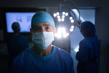 Portrait of a Caucasian male surgeon wearing an operation mask and looking at the camera in the operation theater with coworkers working behind