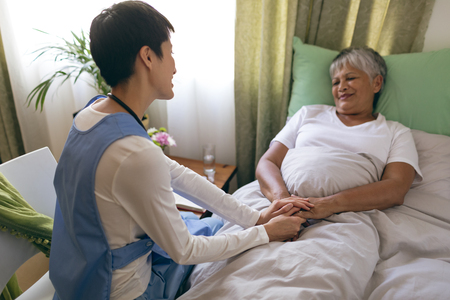 Vista frontal de la enfermera asiática cuidando a una paciente senior de raza mixta en la casa de retiro. Mujer mayor está acostada en la cama.