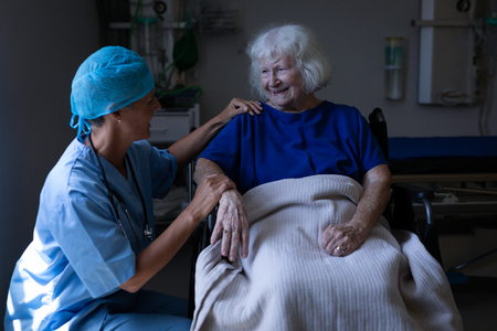 Front view of a Caucasian female surgeon talking to a senior Caucasian patient sitting in a wheelchair in clinic at hospital Imagens
