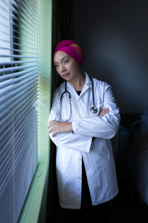 Front view of thoughtful mixed race female doctor looking outside through the window while leaning against a wall Imagens