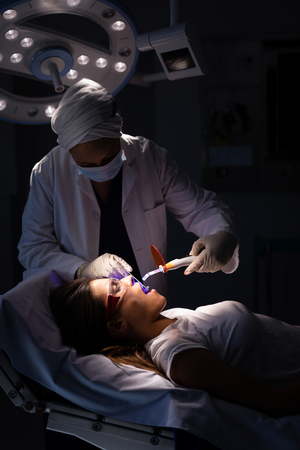 Side view of a mature mixed-race female dentist examining a Caucasian patient with dental curing light in clinic Imagens