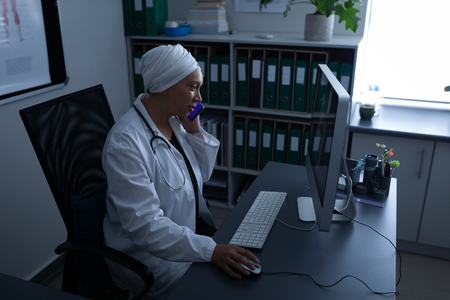 Side view of matured mixed race female doctor talking on mobile phone while working with computer in office at hospital