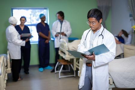 Front view of confident Asian male doctor looking at medical report in clinic at hospital. Colleagues interacting while patient is lying in bed in the background