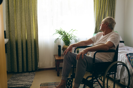 Side view of senior Caucasian male patient  looking outside the window while sitting in wheelchair in bedroom at retirement home
