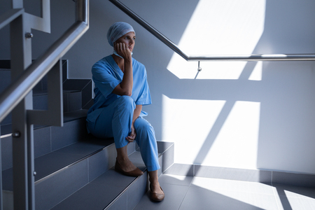 Side view of a thoughtful female surgeon sitting on stairs and holding her head on her had in hospital