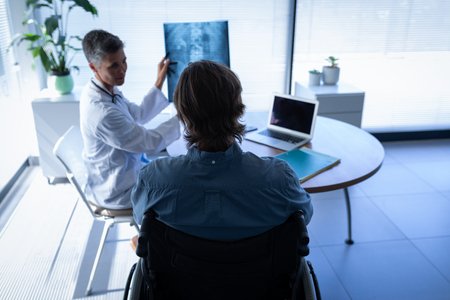 Front view of mature Caucasian female doctor showing x-ray report to disabled patient in wheelchair in  clinic at hospital