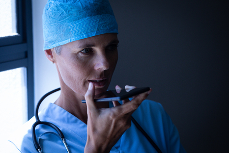 Front view of a Caucasian female surgeon talking on mobile phone at hospital