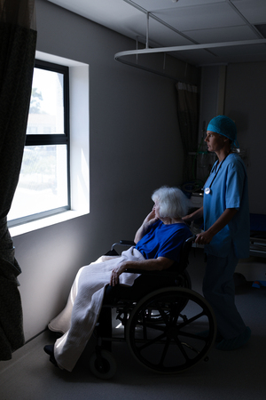 Side view of a Caucasian female surgeon holding the wheelchair of a senior Caucasian patient  while she is looking outside through the window.
