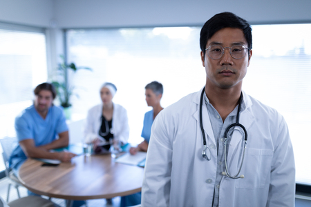 Portrait of smart Asian male doctor standing in clinic at hospital. Colleagues are sitting at a round table in the background Imagens