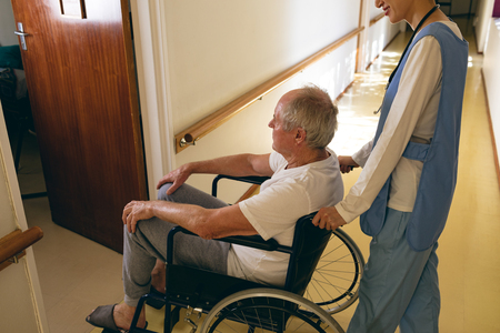 High angle view of  Asian female nurse pushing disabled senior Caucasian  male patient sitting in wheelchair at retirement home Imagens