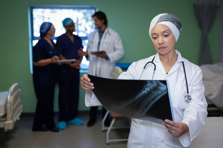 Front view of matured mixed race female doctor looking at x-ray report while colleagues are talking in the background in clinic at hospital Stock Photo