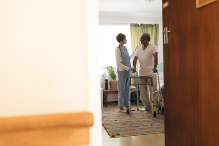 Front view of Asian female nurse talking with African-american senior man while walking with walker at retirement home