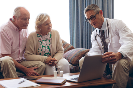 front view of confident male doctor discussing over laptop with senior Caucasian couple at retirement home