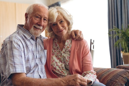 Portrait of happy senior Caucasian couple sitting on sofa at retirement home