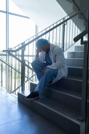 Side view of tensed Caucasian male surgeon with hand on forehead sitting on stairs at hospital Stock Photo - 124669671