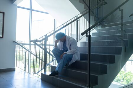 Side view of tensed Caucasian male surgeon with hand on forehead sitting on stairs at hospital Stock Photo